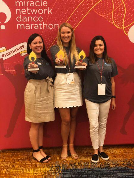Dance Marathon at UF and FSU representatives hold awards given at the 2018 Miracle Network Dance Marathon Leadership Conference