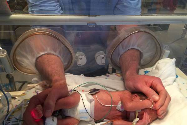 Michael Ossenbeck cradles his son, Andrew, who is supported by a NICU incubator.