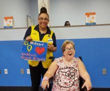 CMN Ambassador Alyssa Mann presents a Walmart employee with a special thank you painting.