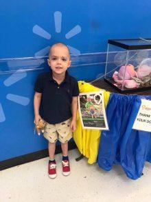 CMN Ambassador Fletcher poses next to his poster at a local Walmart.