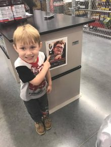 Parker Ayres points at the poster of his brother, Camden.