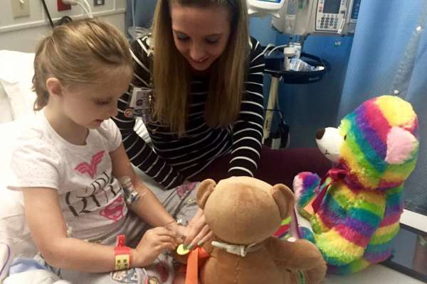 CMN Ambassador Powie looks on as a Child Life specialist demonstrates different procedures on a stuffed teddy bear.