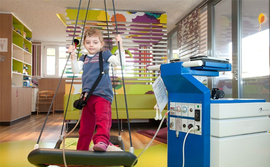 A young patient plays on an indoor swing while connected to an EXCOR machine