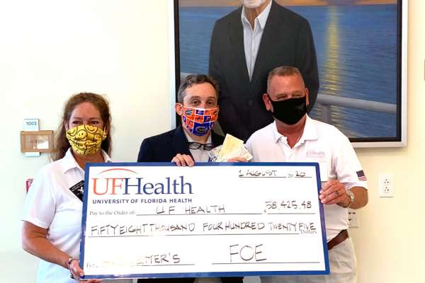 Fraternal Order of Eagles State Worthy President Greg Hall and State Madam President Beth Sapulding-Henschen, along with Dr. Michael Okun, the institute's executive director and the UF College of Medicine's department of neurology chair hold a large check as part of a gift presentation at the Fixel Institute for Neurological Diseases at UF Health.