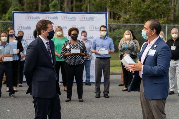 Ed Jimenez, CEO, UF Health Shands accepts a donation of PPE from Harbin Bolton - Vice President, Cox Business Florida / Georgia. The PPE donation Cox is valued around $166,000 dollars.