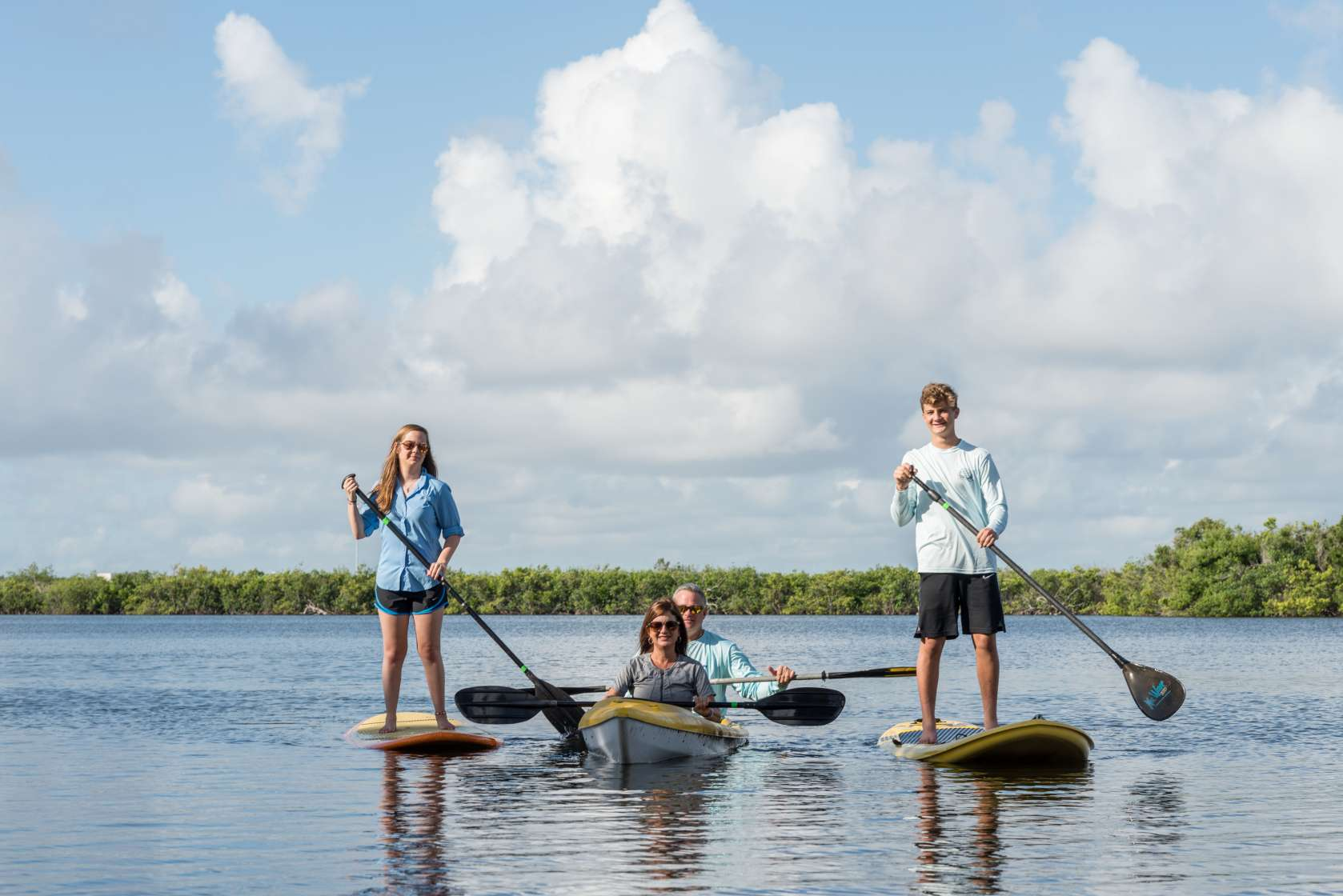 The Cinca family is shown enjoying a day kayaking and paddle boarding on the water.