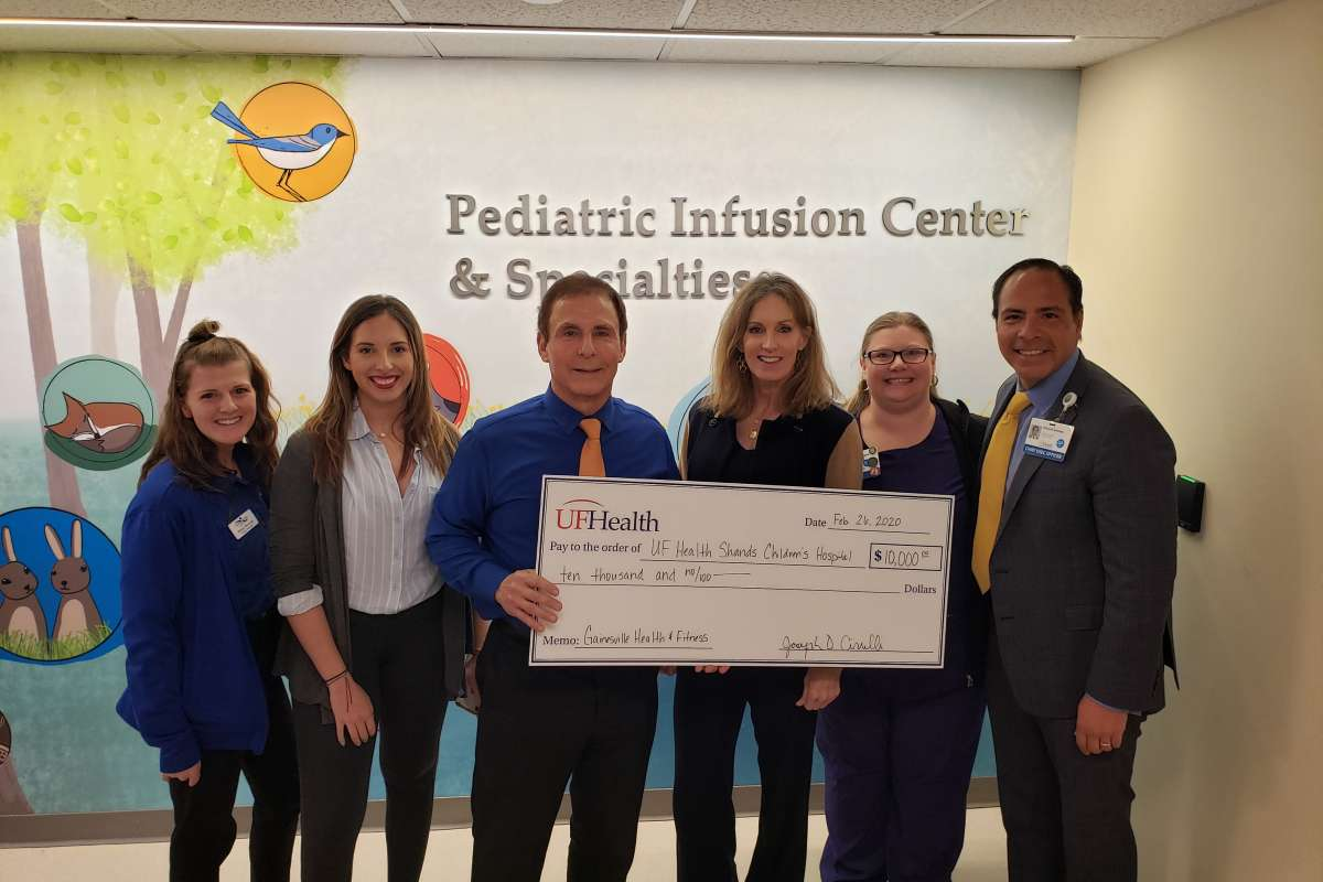 Team members from Gainesville Health and Fitness present a $10,000 check to UF Health Shands Children's Hospital.
