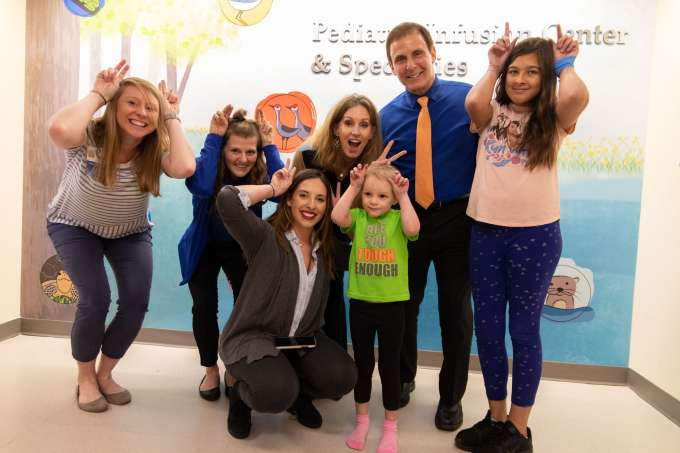 Gainesville Health and Fitness Center staff members and CEO Joe Cirulli take photos with pediatric patients at UF Health Shands Children's Hospital.