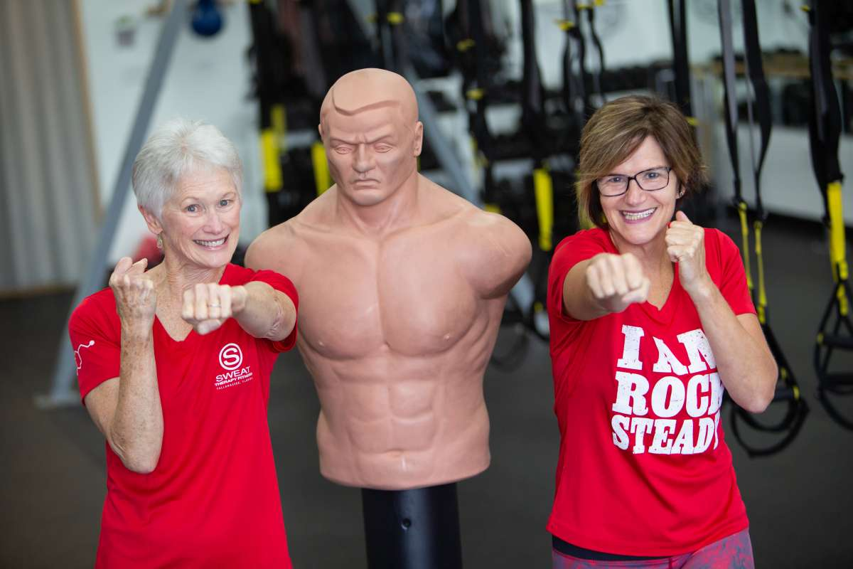 Judith and Kim, wearing red shirts, strike a boxing pose next to a boxing dummy.