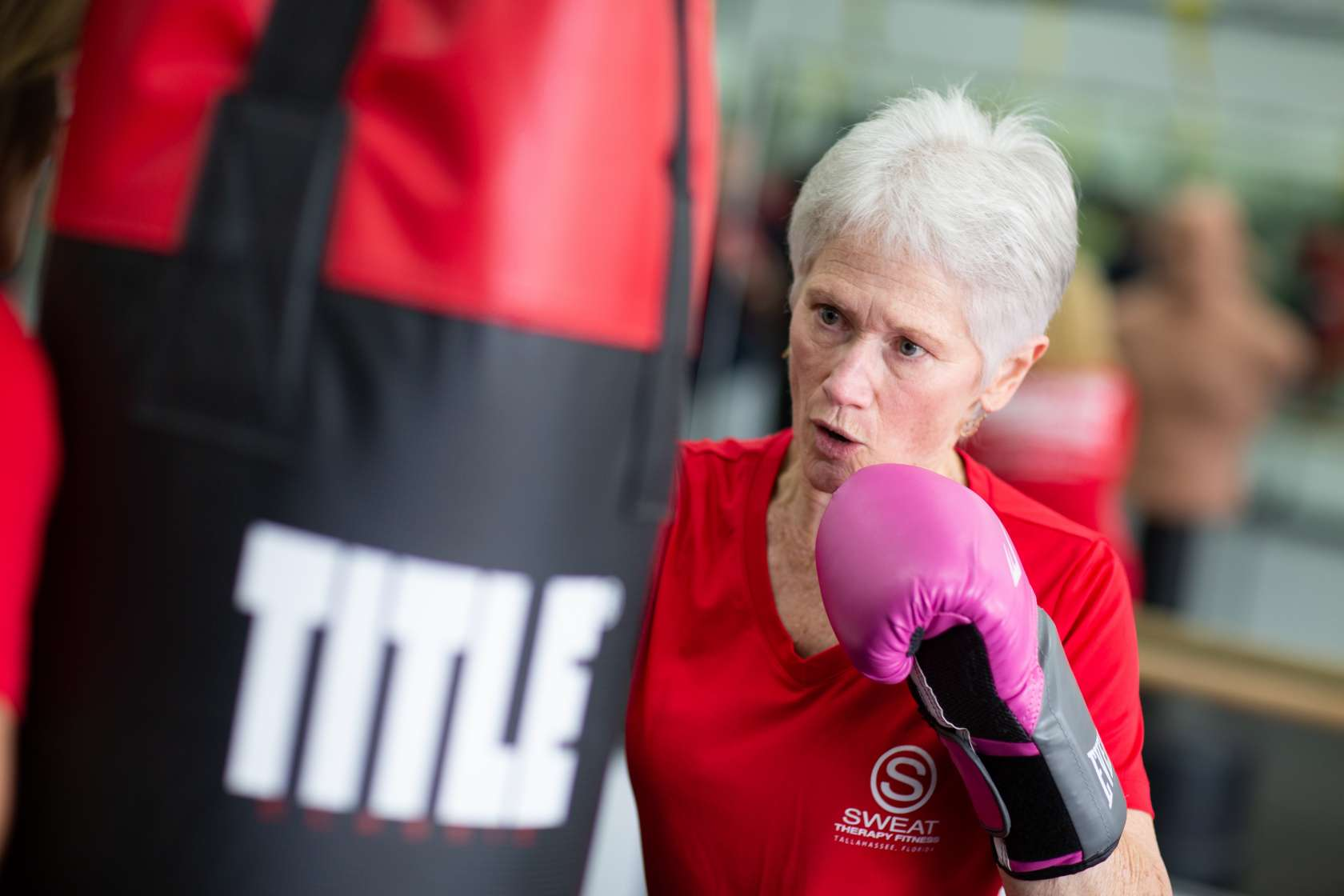 UF Health patient Judith Barrett spars in a boxing class against a bag.