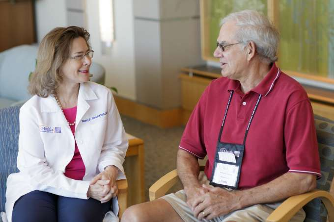 Dr. Nancy Mendenhall sits with a UF Health Proton Therapy Institute patient.