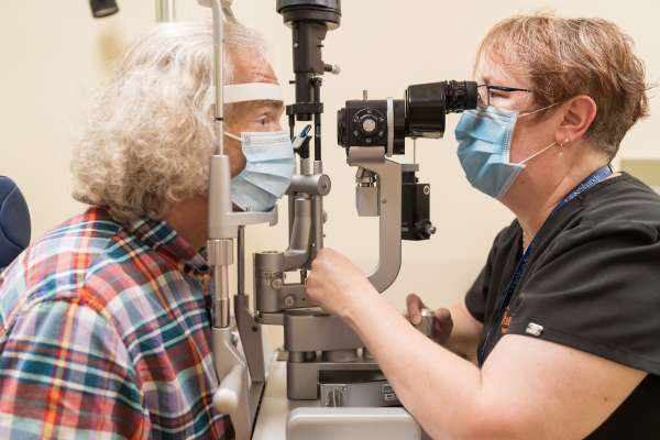 A patient wearing a facemask has his eyes examined by a UF Health care provider.