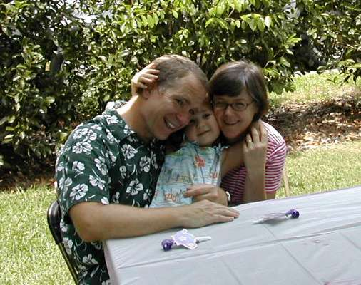 Jon Evans (left) embraces his daughter Kate (middle) and his wife Loree (right).
