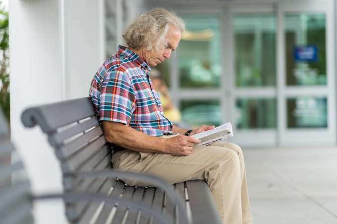 Ophthalmology grateful patient Jon Evans reads a book on a bench outside the UF Health Eye Center.