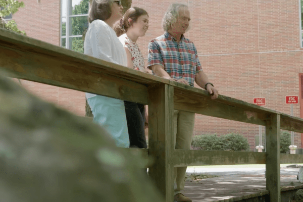 Jon Evans (right) stands on a bridge with his daughter Kate (middle) and his wife Loree (left).