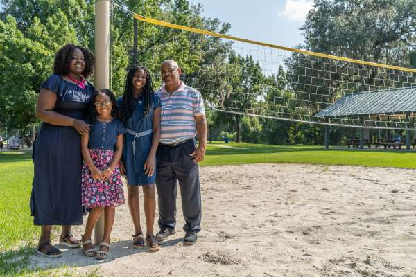 Sydnee Murphy, grateful patient, along with her family stand near a volleyball net.