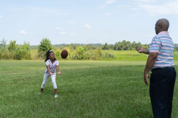 Sydnee catches a football thrown by her father.